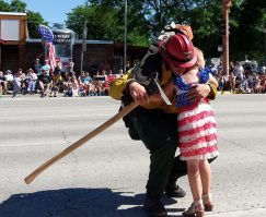 In a touching moment along the parade route, Dad comes over to give his little liberty princess a hug