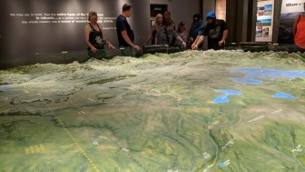 A family making plans are looking over the NE entry (Montana) of the large relief map in the Canyon visitor center