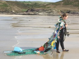Girl on a beach wearing a cape of marine plastic