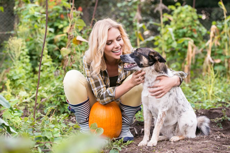 blonde woman kneeling next to a dog