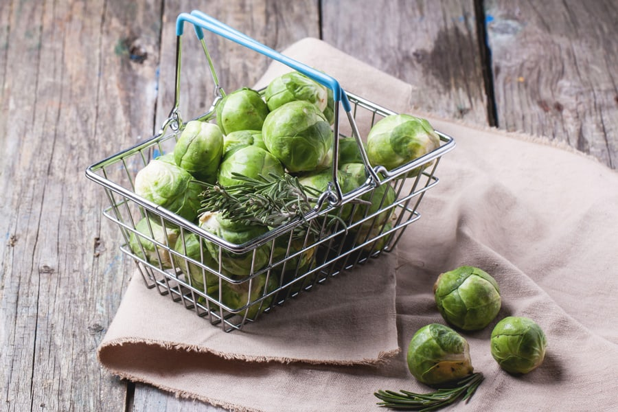 wire basket full of brussels sprouts on a wooden table