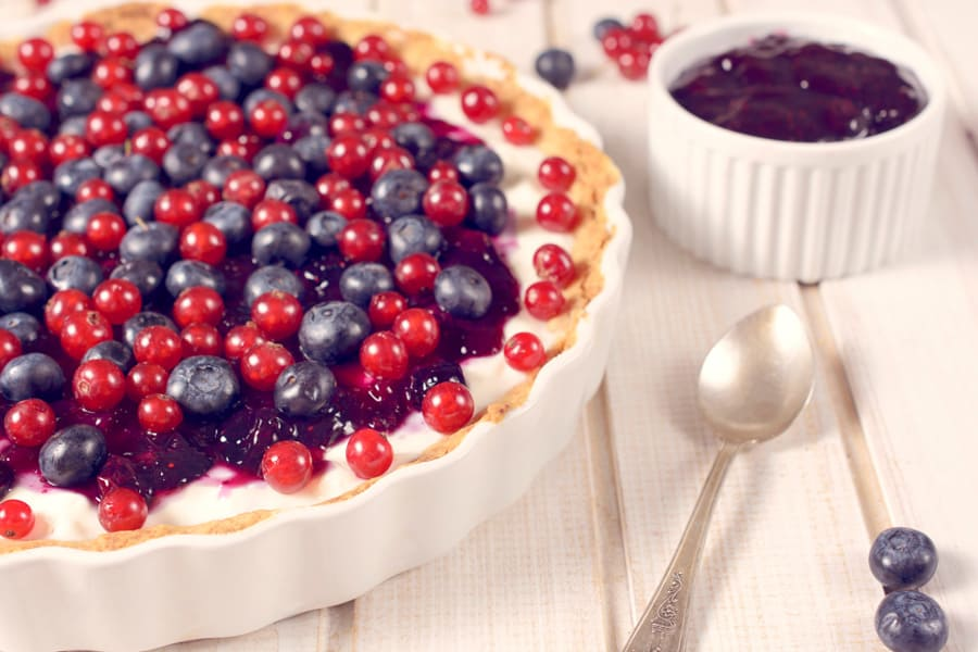 cake with blueberries and cranberries on a white table