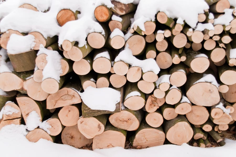 a pile of firewood with snow on it