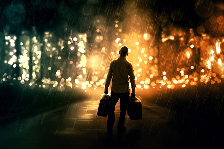 man holding suitcases in the rain