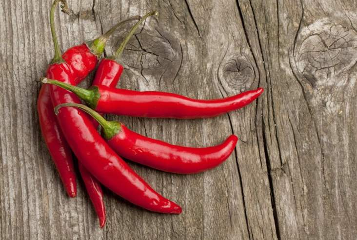 red hot peppers on a wooden background