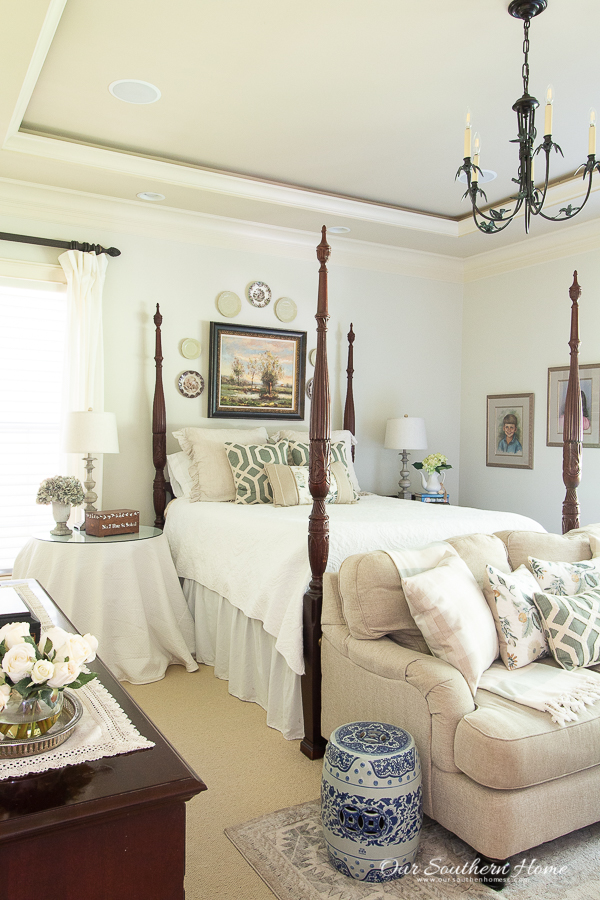 Gray master bedroom decorated for summer with blues and greens with a rice bed