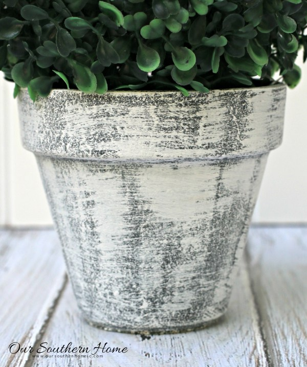 Make an inexpensive centerpiece by applying  a weathered paint treatment to clay pots to create a striking topiary by Our Southern Home