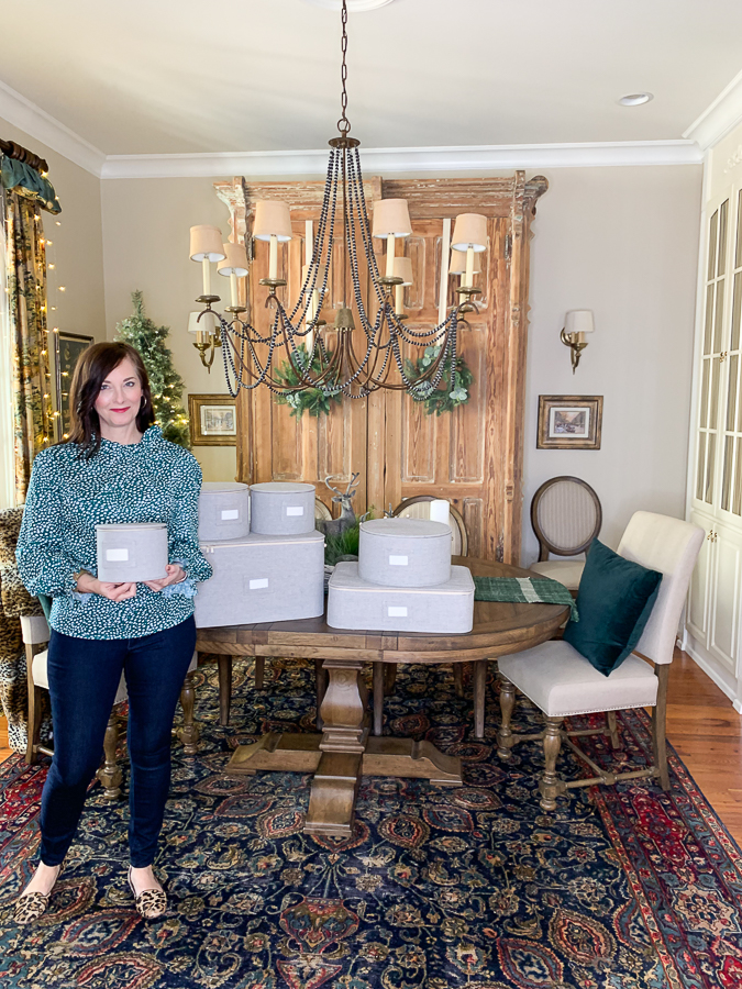 dining room with woman holding storage crates