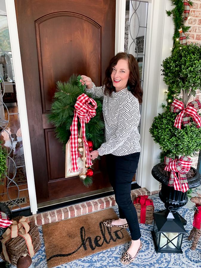 girl putting Chrismtas wreath on front door