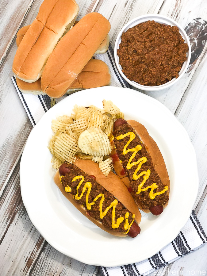 hot dogs with chili and mustard on a white plate with a black and white striped towel