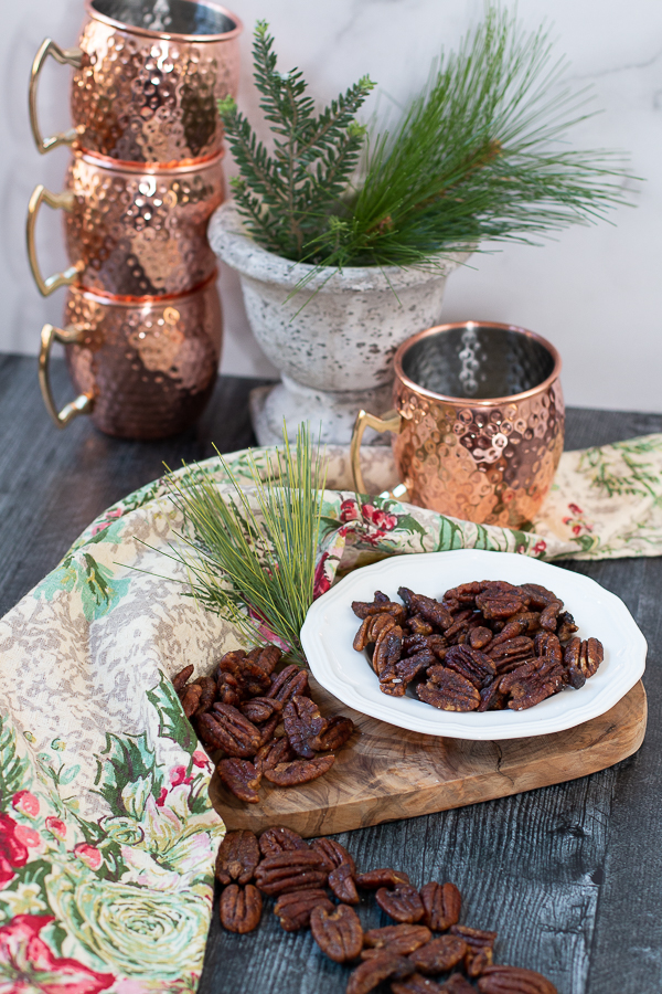 pecans on a dish with copper mugs