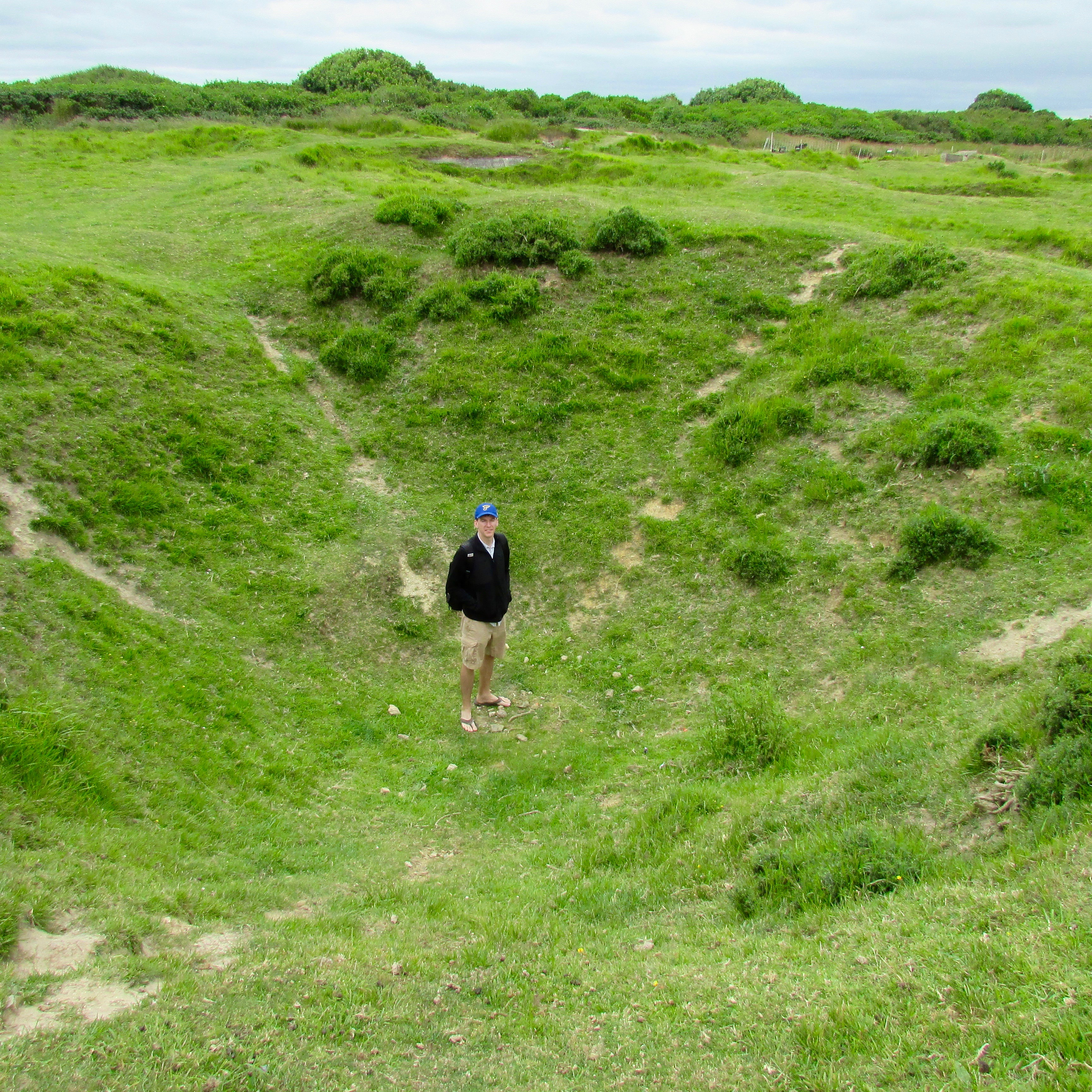 Adam looking small in a bomb crater