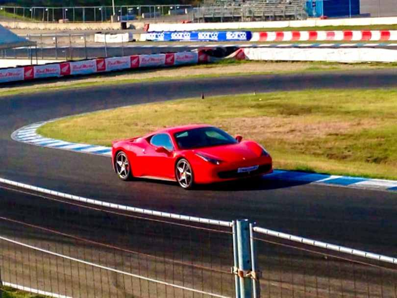 Driving a red Ferrari 458 in Italy on a race track near Milan.