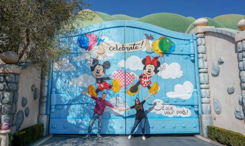 A couple holding hands posing as the Mickey and Minnie mural to celebrate their birthday.