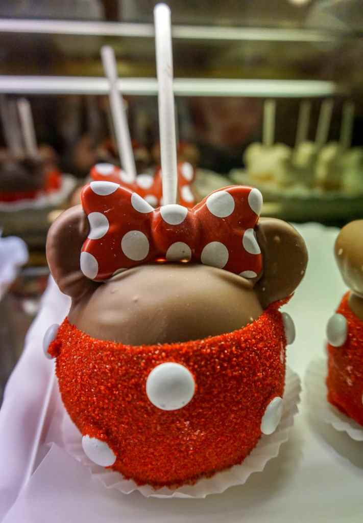 A caramel apple shaped and designed like Minnie Mouse - red sugar sprinkles with white M&ms and a polka dot bow on top.