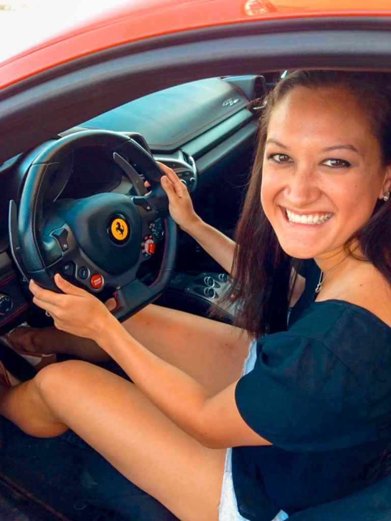 A woman sitting inside a Ferrari 458 smiling.