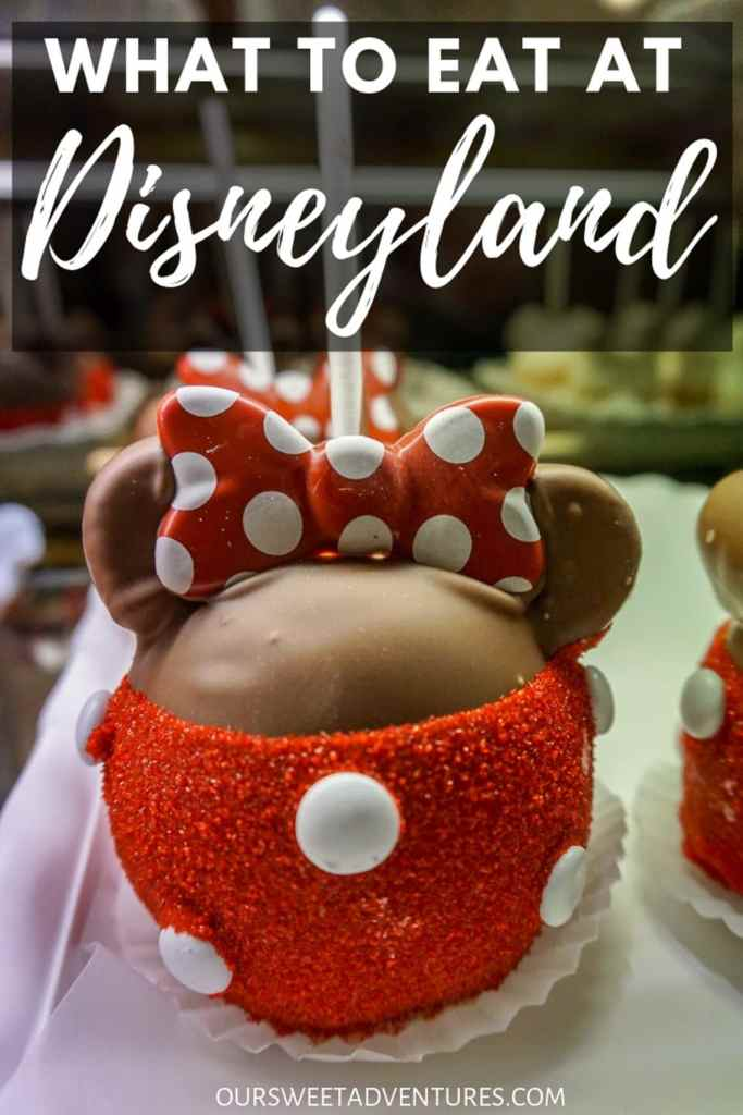 "A chocolate caramel apple with red sugar sprinkles on the bottom with white M&Ms and a bow to resemble Minnie Mouse with text overlay ""What to Eat at Disneyland"""