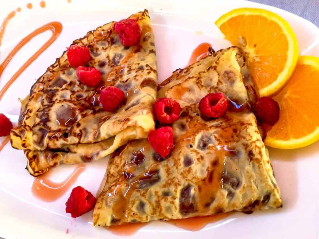 Two crepes shaped in triangles with fresh raspberries and orange slices from CITY Restaurant in Kotor.