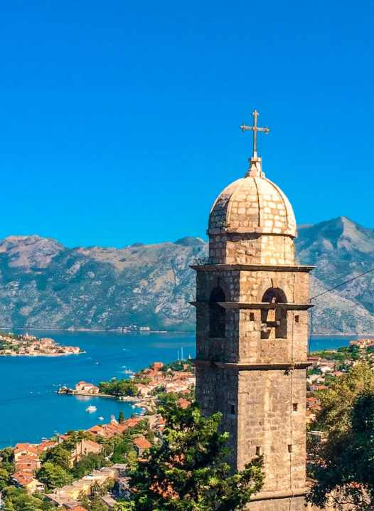 Church of Our Lady of Remedy tower with a small dome towering above the city and Bay of Kotor.