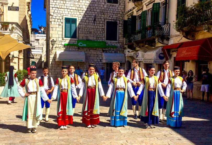 Several locals in Kotor dressed in bright red, blue and green dresses doing their traditional dance in the plaza of Old Town Kotor.