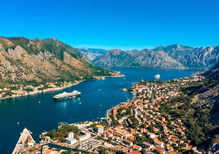 Scenic view of rolling mountains towering over Bay of Kotor's deep blue waters and red roof houses.