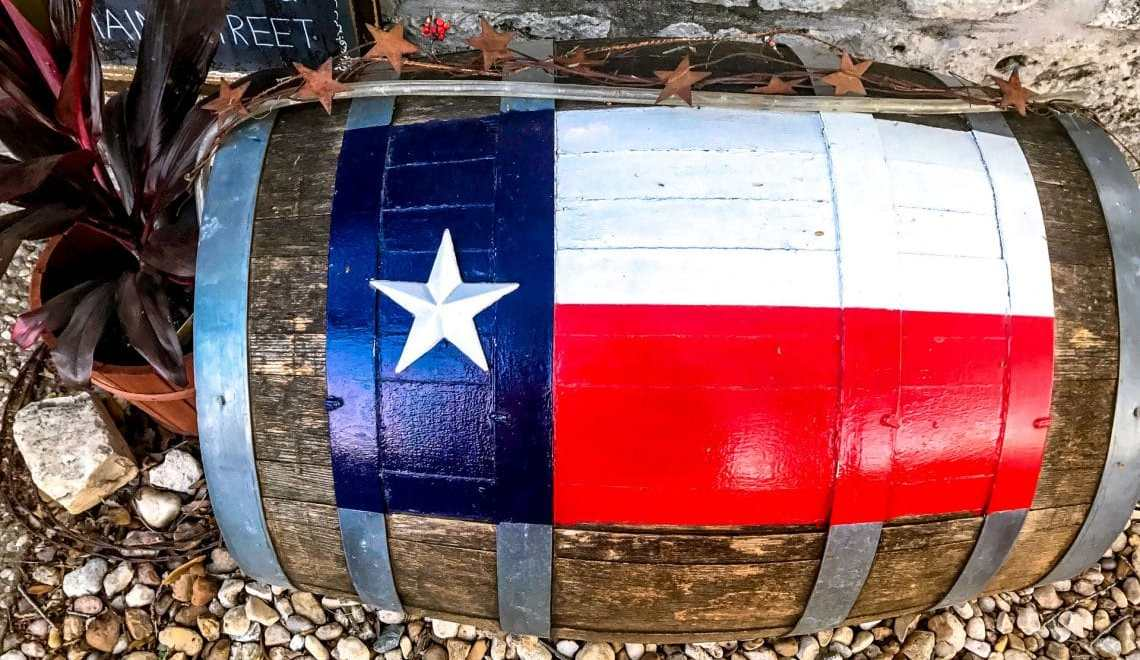 A wine barrel with the Texas flag painted on top.