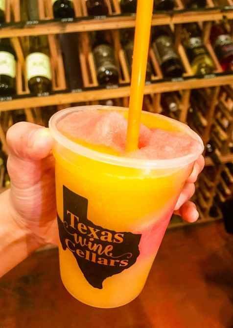 A plastic cup filled with an orange peach Bellini from Texas Wine Cellars.