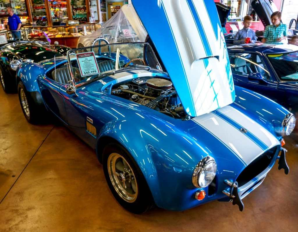 A classic bright blue Shelby Cobra convertible with white stripes in Fast Lane Classic Car's garage.
