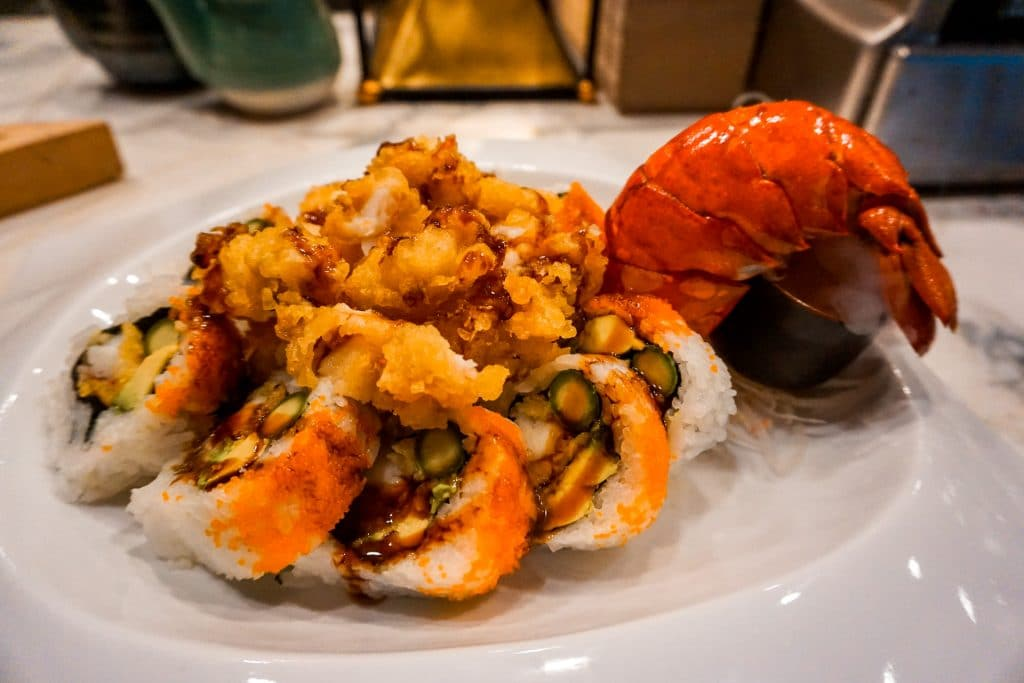 A plate full of lobster tempura, sushi, and a lobster tail from Sushi Marquee.