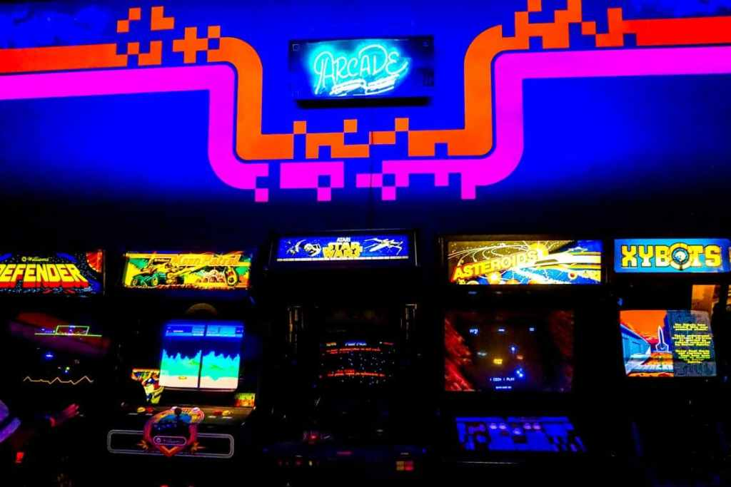 A bright blue and pink neon wall with a row of classic arcade games lined up located at the National Video Game Museum in Frisco.