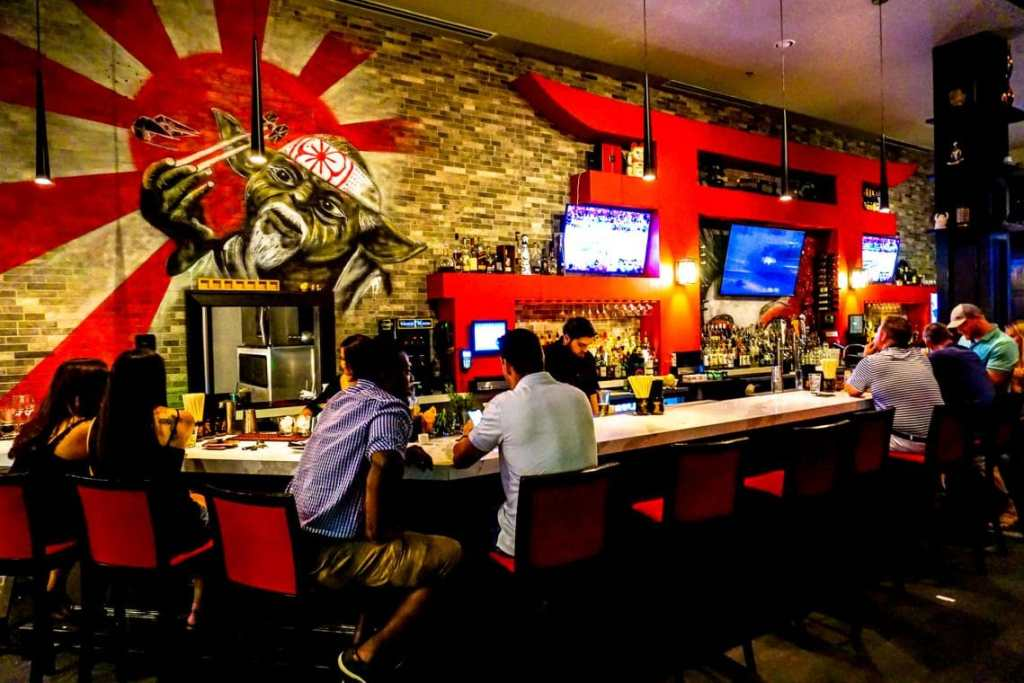 A bar top at Sushi Marquee with people sitting and drinking.
