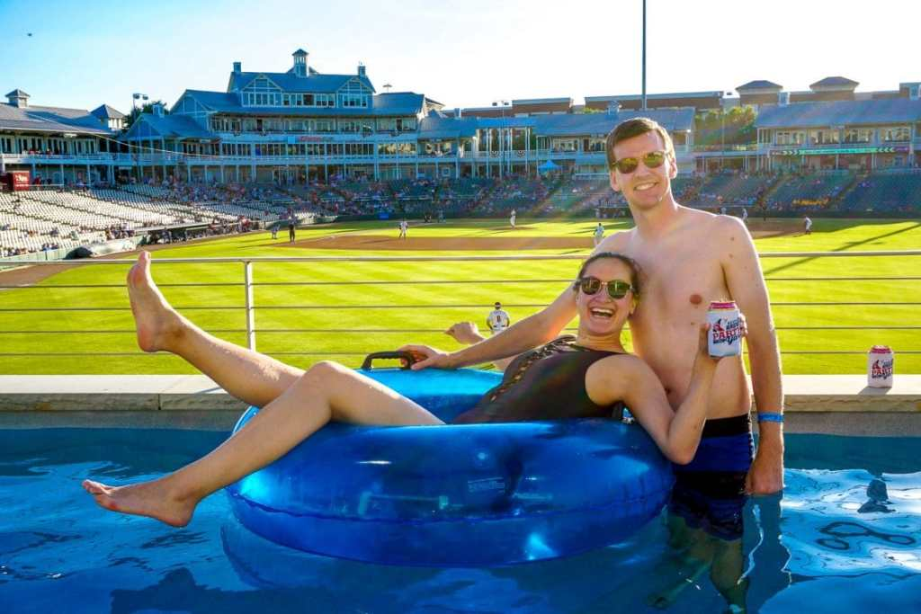 A woman laying inside a blue float with a beer in her hand and a man standing next to her in a lazy river overlooking the RoughRiders baseball game.