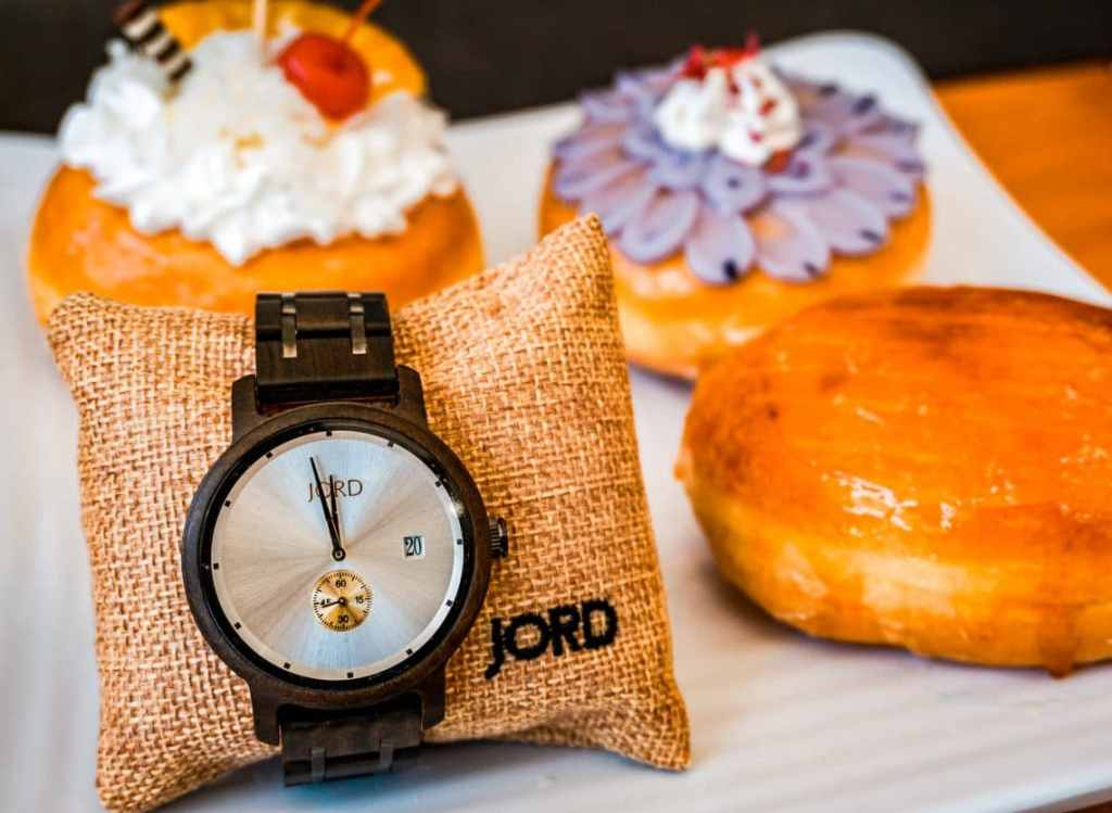 A minimalist wooden watch by JORD with three donuts in the background.