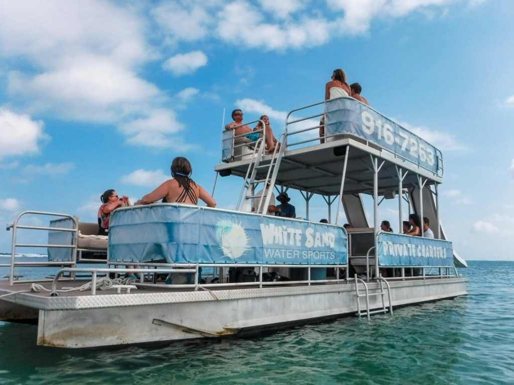 A double-decker pontoon boat with a lot of people onboard - definitely one of the best things to do in the Grand Cayman.