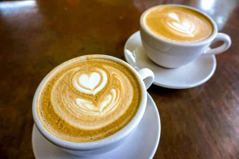 Two pretty cups of lattes in a white mug with a heart flower made of foam from 7th & Park in Brownsville, Texas.