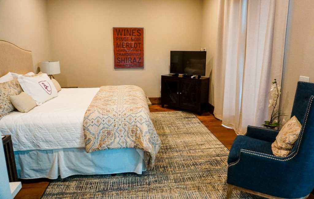 A wide shot of the Barons Creek Vineyards Villa - pictured is a bed on the left, TV stand a blue chair on the right.