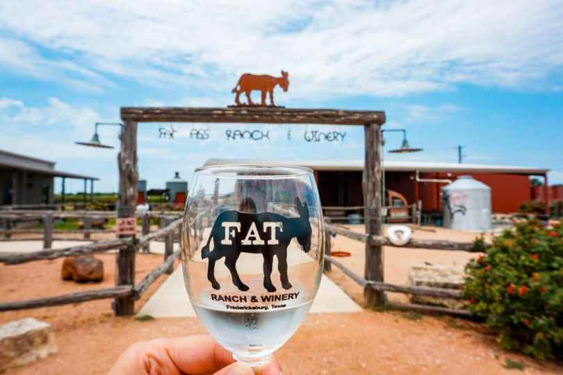 A wine glass with a donkey logo from Fat Ass Ranch and Winery with a ranch in the background.