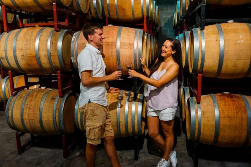 A couple sharing glasses of wine together in the wine cellar at Pedernales Cellars.