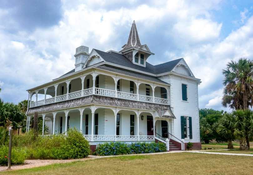 A corner photo of the historical Rabb Plantation house. The house is white with a wrap around porch.