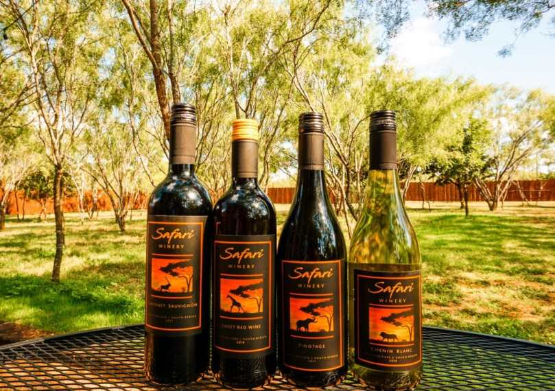 A row of wine bottle from Safari Winery with trees in the background.