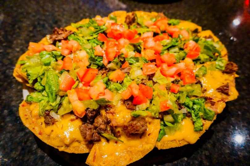 One of the best things to do in Brownsville is visit the Vermillion and eat their famous nachos as pictured - handmade tortilla chips covered in beans, cheese, diced tomatoes, and lettuce.