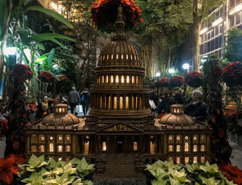 The U.S. Capitol building made of plant-based materials with rows of greenery in the background. You can find this attraction in Washington D.C. in the winter at the U.S. Botanical Garden.