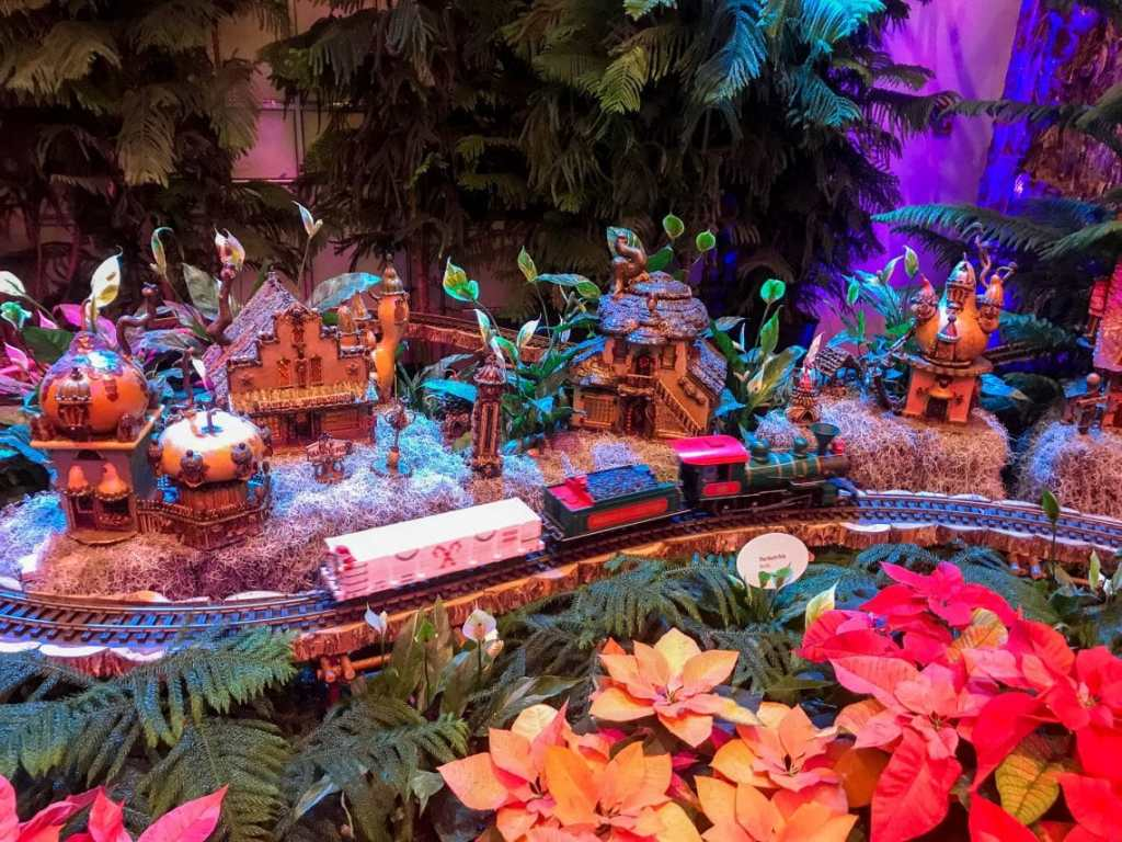 A train model passing through a colorful town at Washington D.C.'s National Botanical Garden during Seasons Greenings - one of the best things to do in Washington D.C. in the winter.