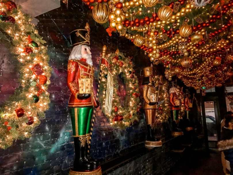 A decorated room filled with wreathes and nutcrackers on the wall from Drink Company's Miracle on 7th Street pop-up bar in Washington D.C.