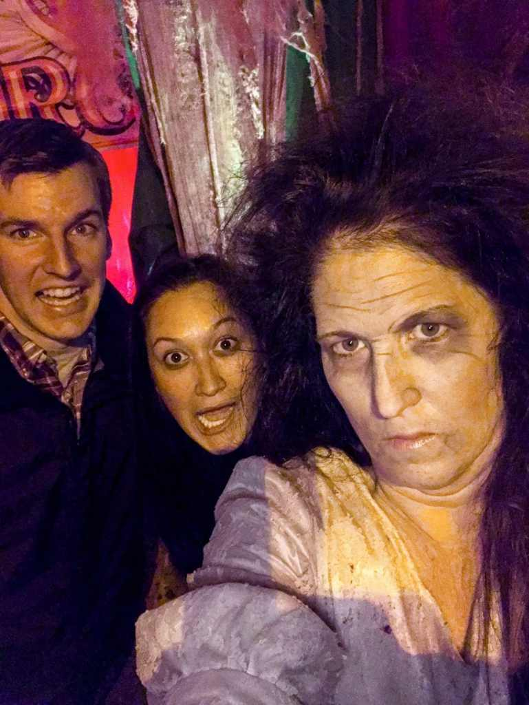 A couple acting scared taking a selfie with a scary woman/actress at a haunted house in Washington D.C.