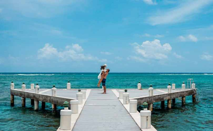 A man lifting a woman on the pier near the ocean.