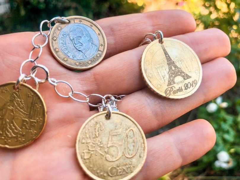 A hand holding foreign currency turned into a beautiful bracelet from Mariamor Designs.