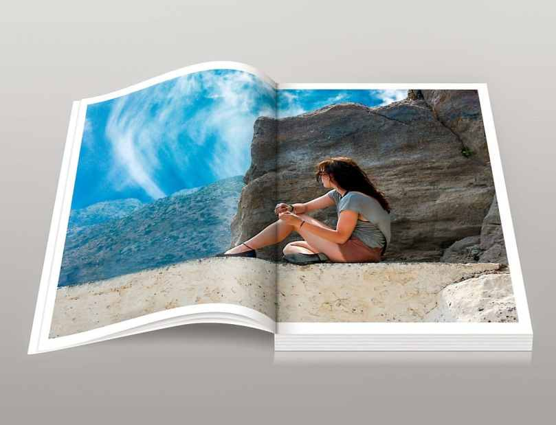 An open photo book of a woman sitting near a rock.