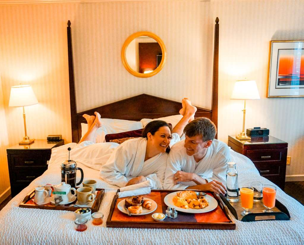 A couple enjoying room service breakfast in bed at The Listel Hotel - the perfect place to stay in Vancouver.