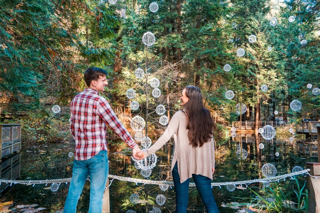 A couple holding hands and staring into each others eyes with white sparkling balls hanging above a pond with a rainforest in the background at Capilano Suspension Bridge Park.